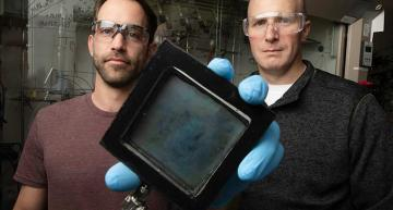 NREL Researcher Lance Wheeler (left) holds a sample of the SwitchGlaze technology alongside Robert Tenent, the laboratory's program lead for window technology.