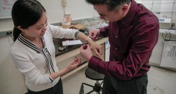 Materials science and engineering professor Xudong Wang fits a new wound dressing around the wrist of graduate student Yin Long. The device stimulates healing using electricity generated from the body's natural motions. Photo courtesy of UW-Madison, Sam Million-Weaver.