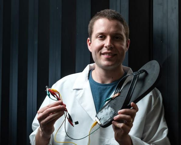 Rice University postdoctoral researcher Michael Stanford holds a flip-flop with a triboelectric nanogenerator, based on laser-induced graphene, attached to the heel. Walking with the flip-flop generates electricity with repeated contact between the generator and the wearer's skin. Stanford wired the device to store energy on a capacitor. Photo by Jeff Fitlow