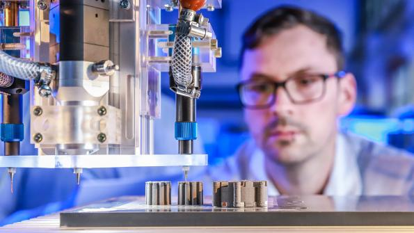 Johannes Rudolph observes the multimedia 3D-printing of an electrical machine in the lab. This is the first time copper, ceramics and iron have been used simultaneously in the printing process. On the left are the rotors and the stator is on the right. Photo: Jacob Müller