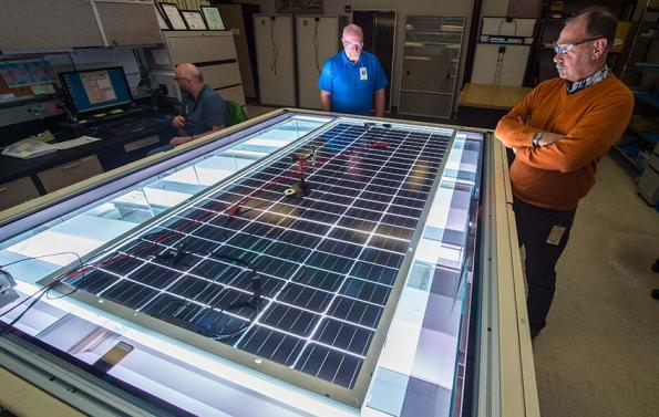 Allen Anderberg (left), Steve Rummel, and Dean Levi of NREL's Cell and Module Performance group measure the power output of a PV module on NREL's solar simulator. Photo by Dennis Schroeder, NREL